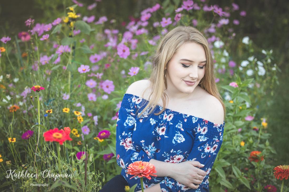 Senior girl sitting in wildflower garden   Potsdam NY senior photographer