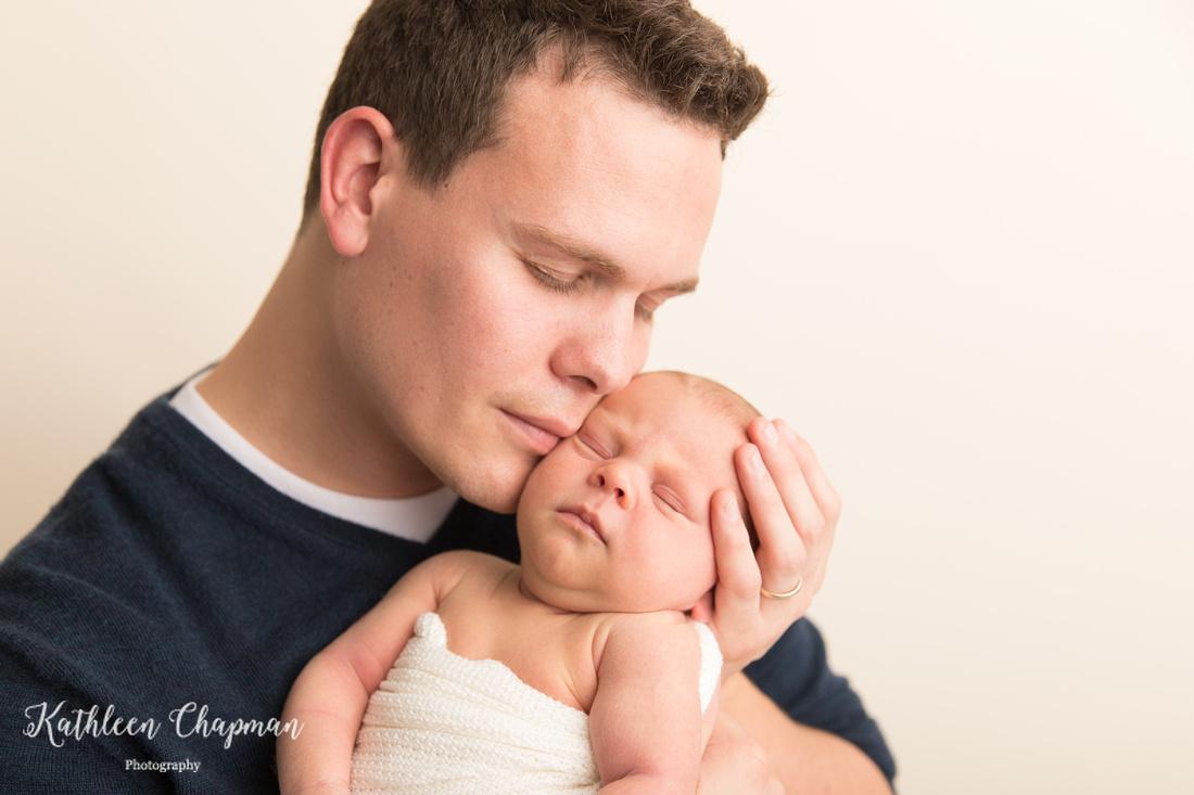 Father kissing newborn son   Massena NY newborn photographer