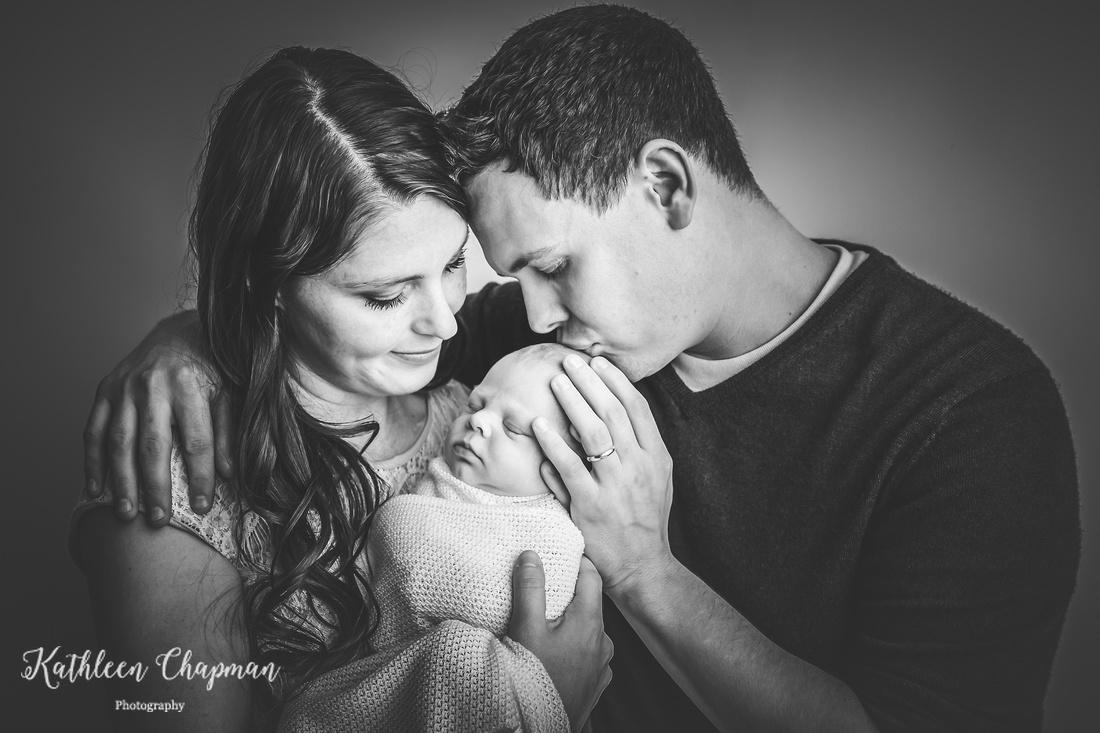 Dad kissing newborn son   Massena NY family photographer