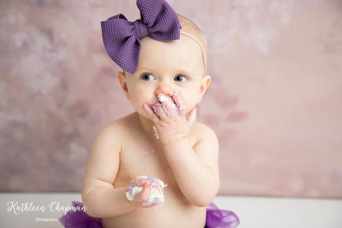 Baby girl eating cake at cake smash session | Malone NY child photographer