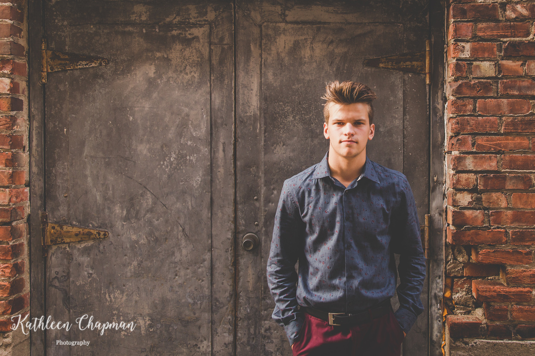 Senior guy in alley by cool door in Massena NY Potsdam NY family photographer