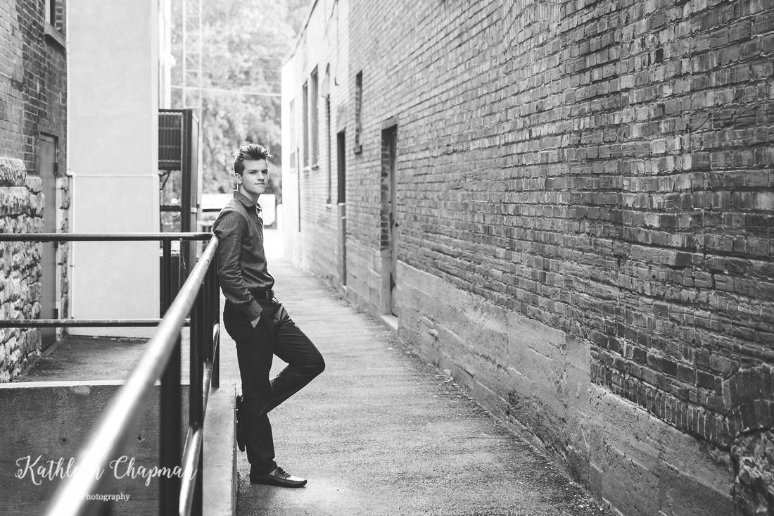 Senior boy leaning on railing in brick alley in Massena NY Potsdam child photographer