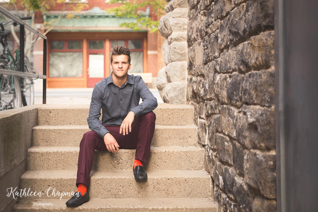 Senior guy smiling sitting on steps in brick alley in Potsdam NY St. Lawrence County family photographer