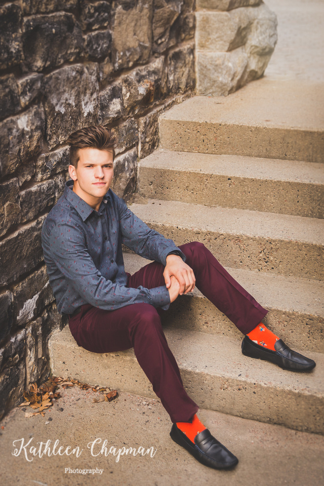 Senior guy with serious expression on steps in brick alley in Massena NY Potsdam child photographer
