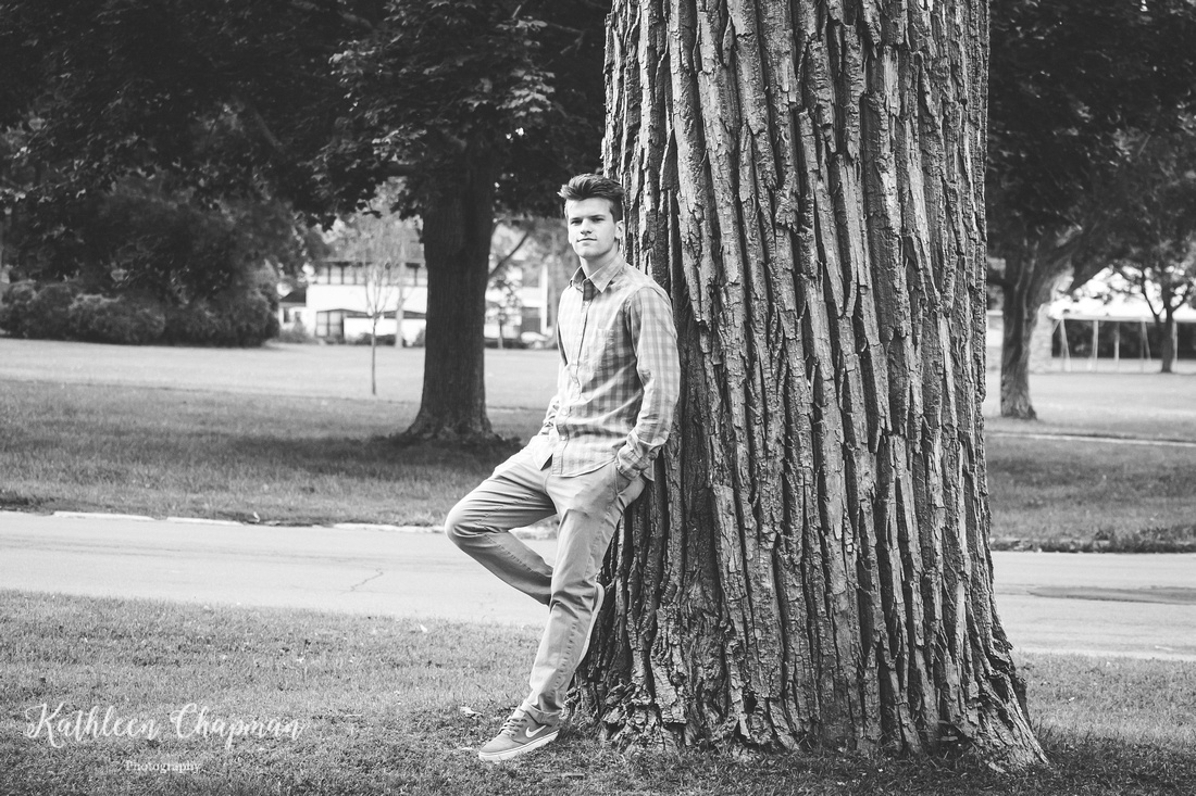 Black and white portrait of senior guy in park by big tree in Massena, NY Potsdam child photographer