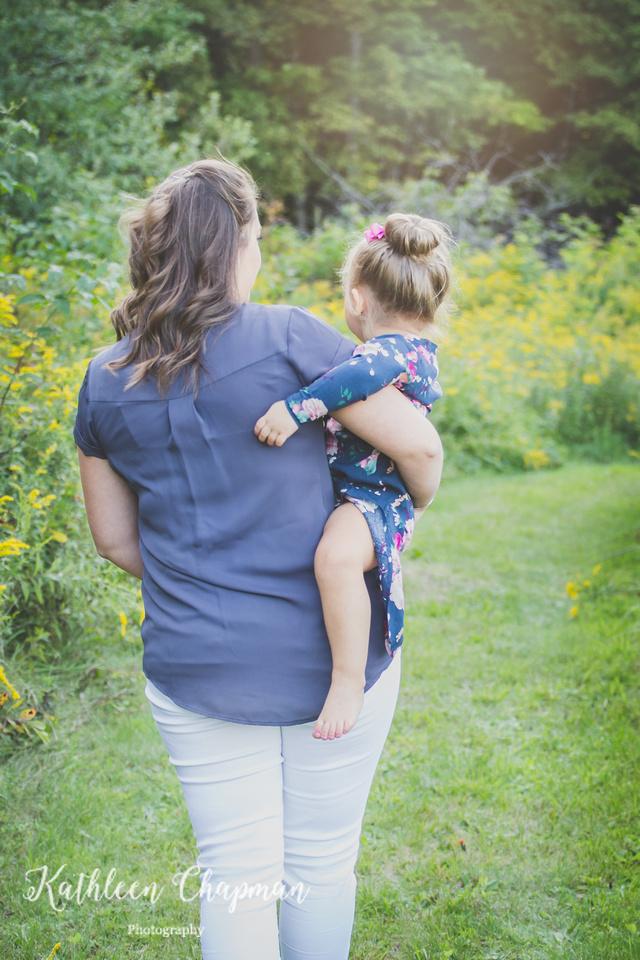 Mother holding daughter in wild flower garden Potsdam NY family photographer