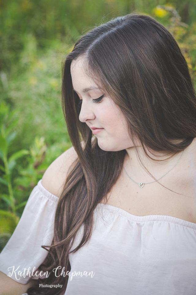 Beautiful senior girl with long brown hair in wild flower garden potsdam ny child photographer