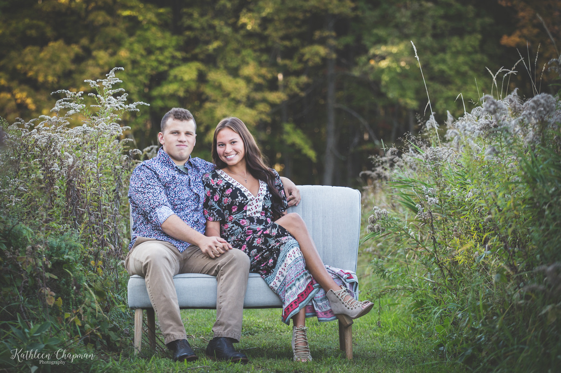 young couple on couch in field massena ny family photographer