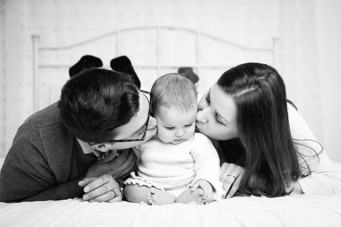 parents kissing baby girl on bed potsdam ny child photographer